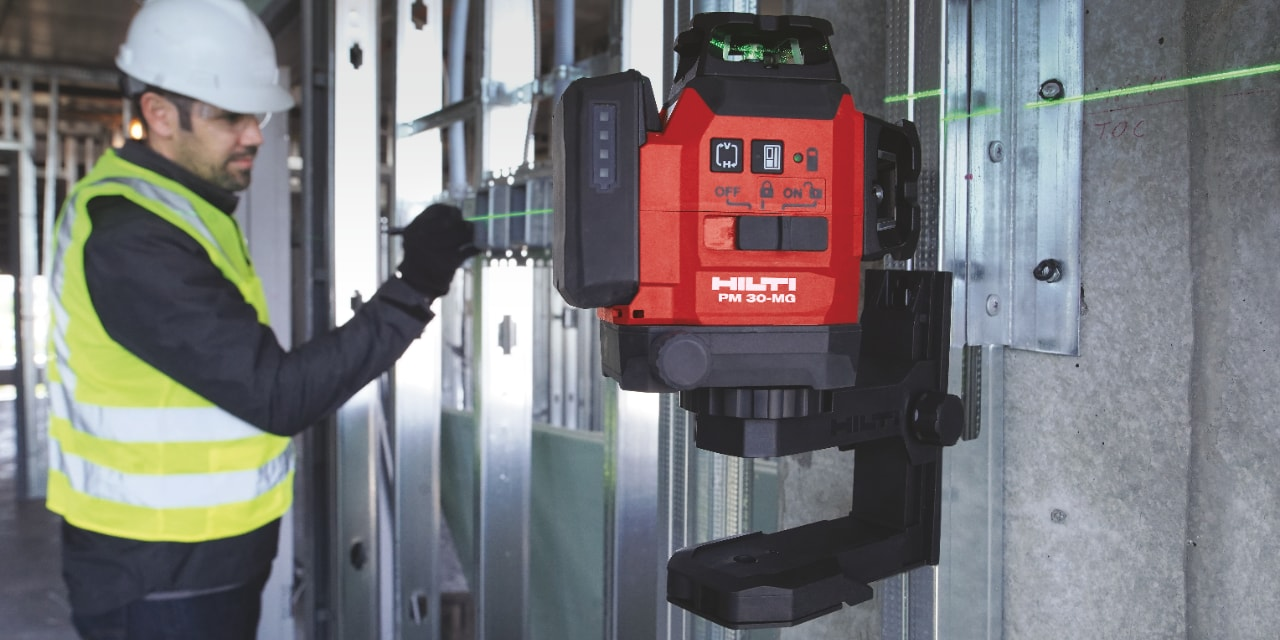 A worker operates a Hilti measuring tool